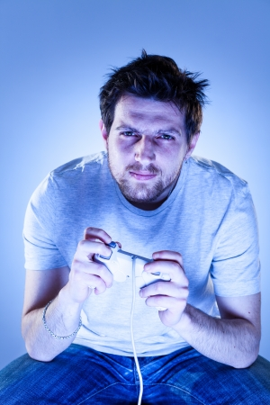 gamepad: Concentrated Man Playing Viodegames with Gamepad Stock Photo