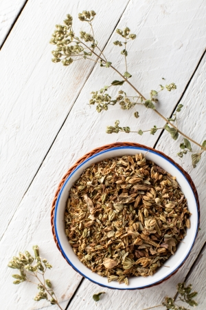 oregano plant: Dried Oregano in a Bowl on White Wood