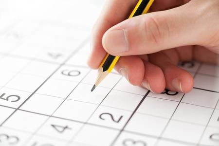 Hand met een potlood Spelen Sudoku