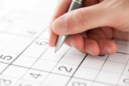 Hand Holding a Pen Playing Sudoku 版權商用圖片