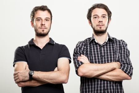 bros: Two Serious Twins with Arms Folded