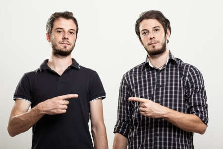 25 to 30: Two Serious Twins Pointing Each Other Stock Photo