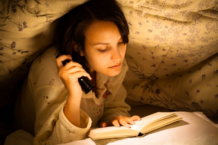 Serious Woman Reading a Book with Flashlight on Bed Banco de Imagens