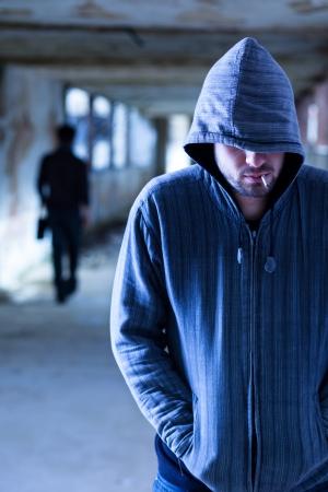 man smoking: Smoking Criminal with Hood Walking in a Slum Corridor