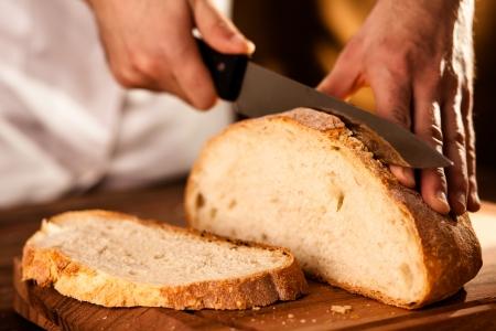 Baker Slicing Bran Bread on a Cutting Board Stock Photo - 17276482