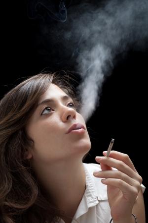 chica fumando: Mujer que fuma un cigarrillo en el fondo Negro
