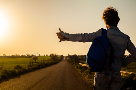 若い男が、国の道路上でヒッチハイク 写真素材