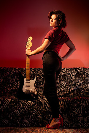 Sexy Pin Up with Electric Guitar on Couch photo