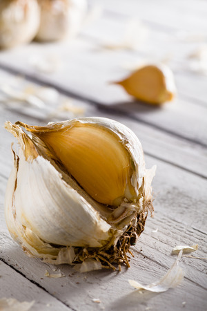orange peel clove: Raw Clove of Garlic on White Wood