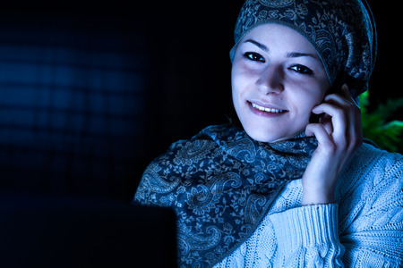 middle eastern woman: Smiling Middle Eastern Woman with Computer and Headset at Night Stock Photo