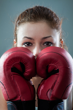 worn: Boxing Woman Behind Two Worn Out Gloves Stock Photo