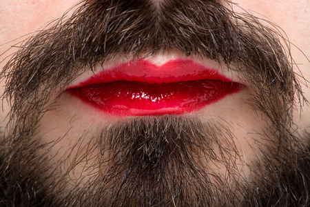 mouth close up: Mans Mouth with Red Lipstick on His Lips and Brown Beard Stock Photo