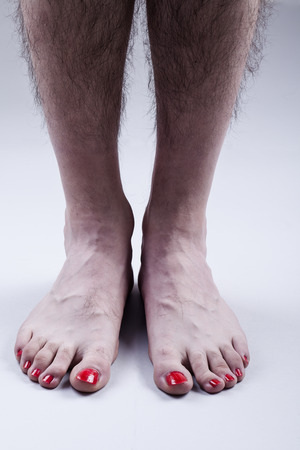 Mans Feet with Red Nail Polish and Hairy Legs on Bright Gray Background
