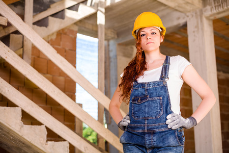 women s legs: Confident Woman Bricklayer with Overalls and Helmet with Her Hands on Hips