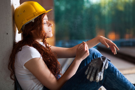 house worker: Woman Bricklayer with Overalls and Helmet Smoking a Cigarette