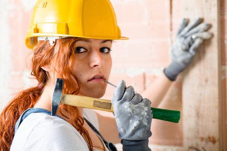 women s legs: Woman Bricklayer with Helmet Holding a Hammer in Her Hand Stock Photo