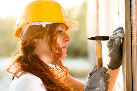 women s legs: Woman Bricklayer with Helmet Hitting a Nail with a Hammer Stock Photo