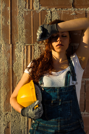 bricklayer: Tired Woman Bricklayer with Overalls and Helmet Standing in Front of a Brick Wall Stock Photo