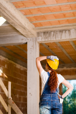 bricklayer: Woman Bricklayer with Overalls and Helmet Watching Upstairs Stock Photo