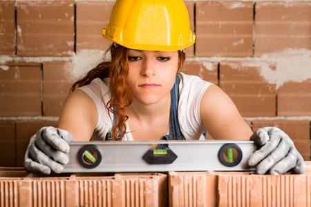レンガの壁に精神のレベルを保持しているヘルメットと女性職人