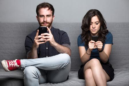 falda: Pareja silencioso joven con Smartphones sientan en un sofá