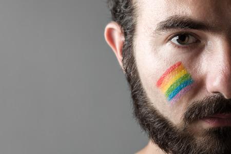 彼の頬は、同性愛者の権利のシンボルを描いた虹を持つ男 写真素材