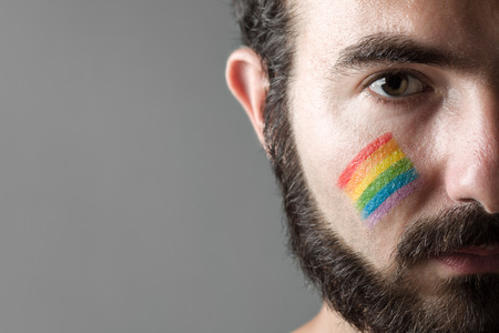 face paint: Man with Rainbow Painted on His Cheek, Symbol of Gay Rights