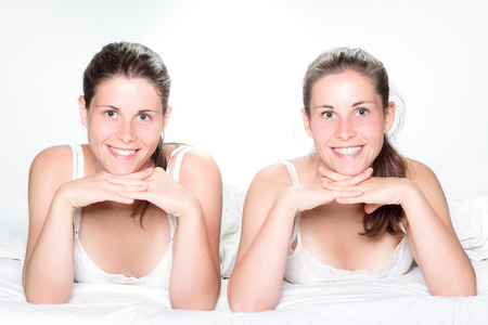 twin sister: Two Smiling Twin Sisters Laying on Bed Stock Photo
