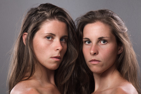 sisters sexy: Two Serious Twin Sisters Looking at Camera