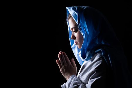 검은 배경에기도하는 푸른 베일과 성모 마리아 스톡 콘텐츠