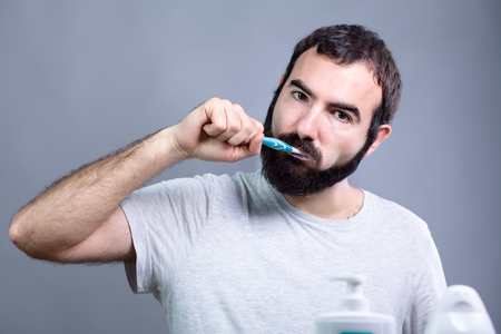 toothpaste: Man with Beard Washing His Teeth with a Toothbrush Stock Photo
