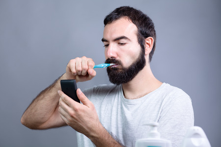 eyes looking down: Man with Beard Washing His Teeth with a Toothbrush while Watching a Smartphone