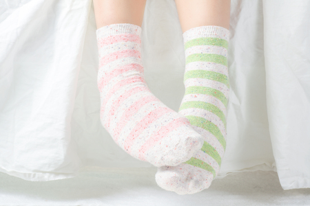 girl socks: Womans Feet with Unpaired Striped Socks Stock Photo