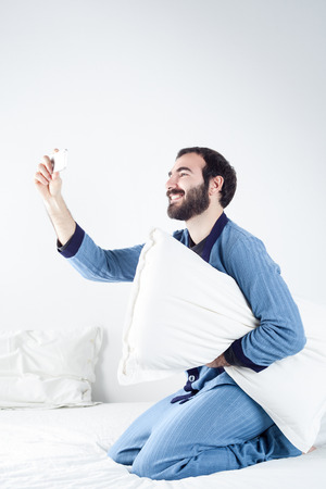 sleepwear: Man with Pajamas on Bed Taking a Selfie with a Smartphone Stock Photo