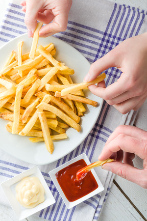 Drie Handen Picking Frieten en dompelen in Ketchup en Mayonaise Stockfoto