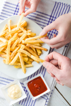 fry: Three Hands Picking French Fries with Ketchup and Mayonnaise Stock Photo