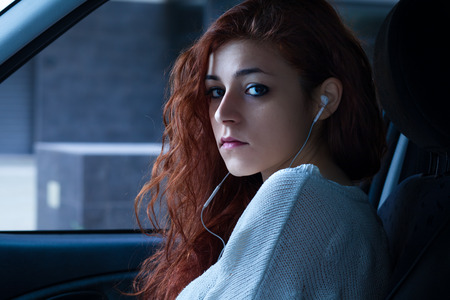 earpiece: Redhead Woman with Earbuds Sitting in a Car