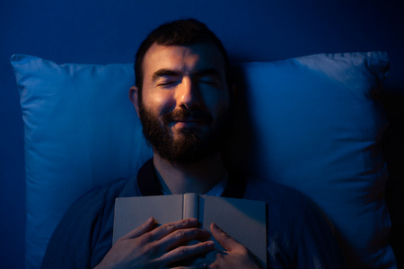 brown hair blue eyes: Smiling Man Sleeping with a Book on His Chest