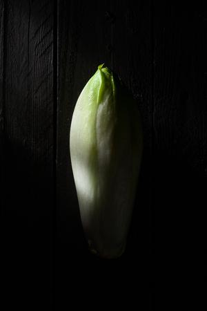 escarola: Endivia en la madera Negro Foto de archivo