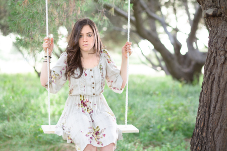 pretty brunette woman: Serious Woman Sitting on a Swing in a Park