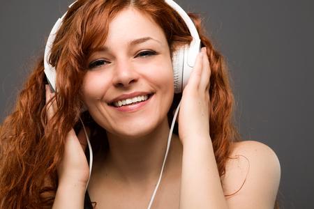 listening to music: Redhead sonriente mujer de escuchar música con auriculares