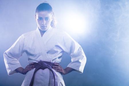 Zekere Vrouw dragen van Karate Kimono met haar handen op haar heupen
