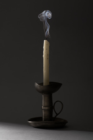 blown: Blown Out Smoking Candle on Iron Candlestick
