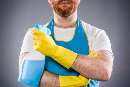 hairy arms: Cleaner Man with Arms Crossed Holding a Detergent Wearing an Apron and Plastic Gloves Stock Photo