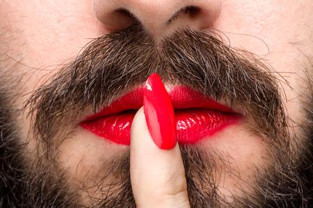 dedo indice: El hombre barbudo con el lápiz labial rojo en los labios y esmalte de uñas hace gesto del silencio Foto de archivo
