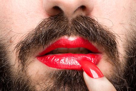 彼の唇と爪のポーランド語の赤い口紅が付いて髭の男