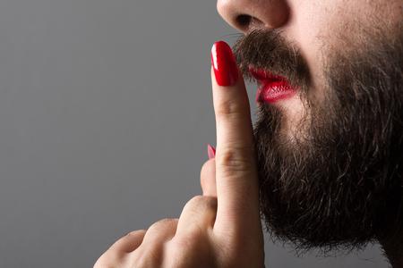 Bebaarde man met rode lippenstift op zijn lippen en nagellak Stilte gebaar maken Stockfoto