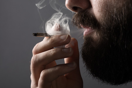 man with beard: Detail of a Man with a Beard Smoking a Cigarette