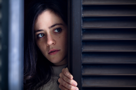 Worried Woman Watching Outside from a Wooden Window Shutter 스톡 콘텐츠