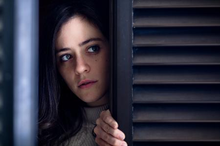 Ongerust gemaakte vrouw die buiten een houten vensterluiter kijkt